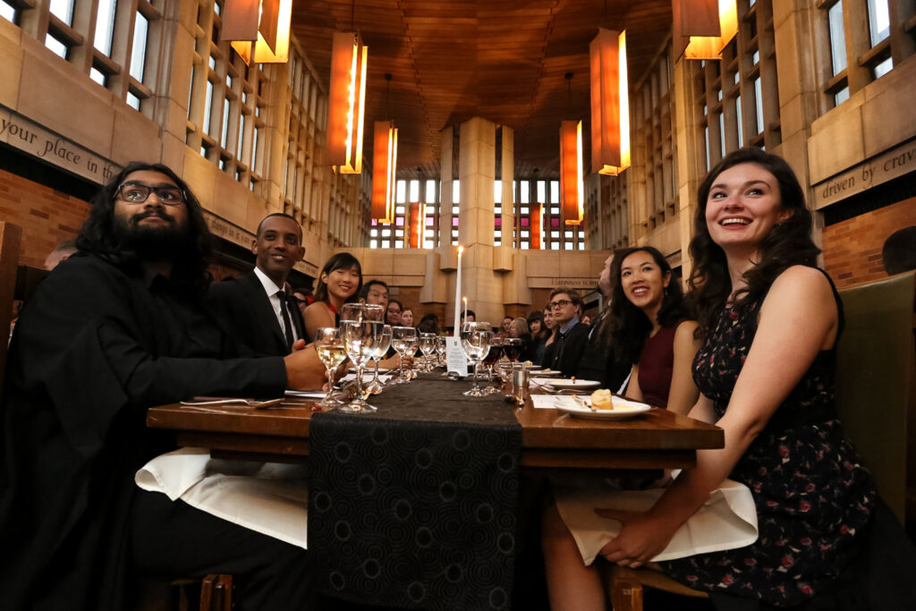 Group of Junior Fellows sitting at a long table smiling at something off camera