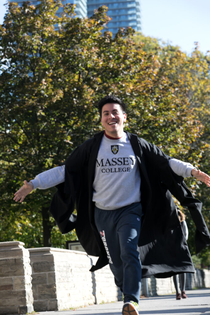 Man running in his Massey College gown